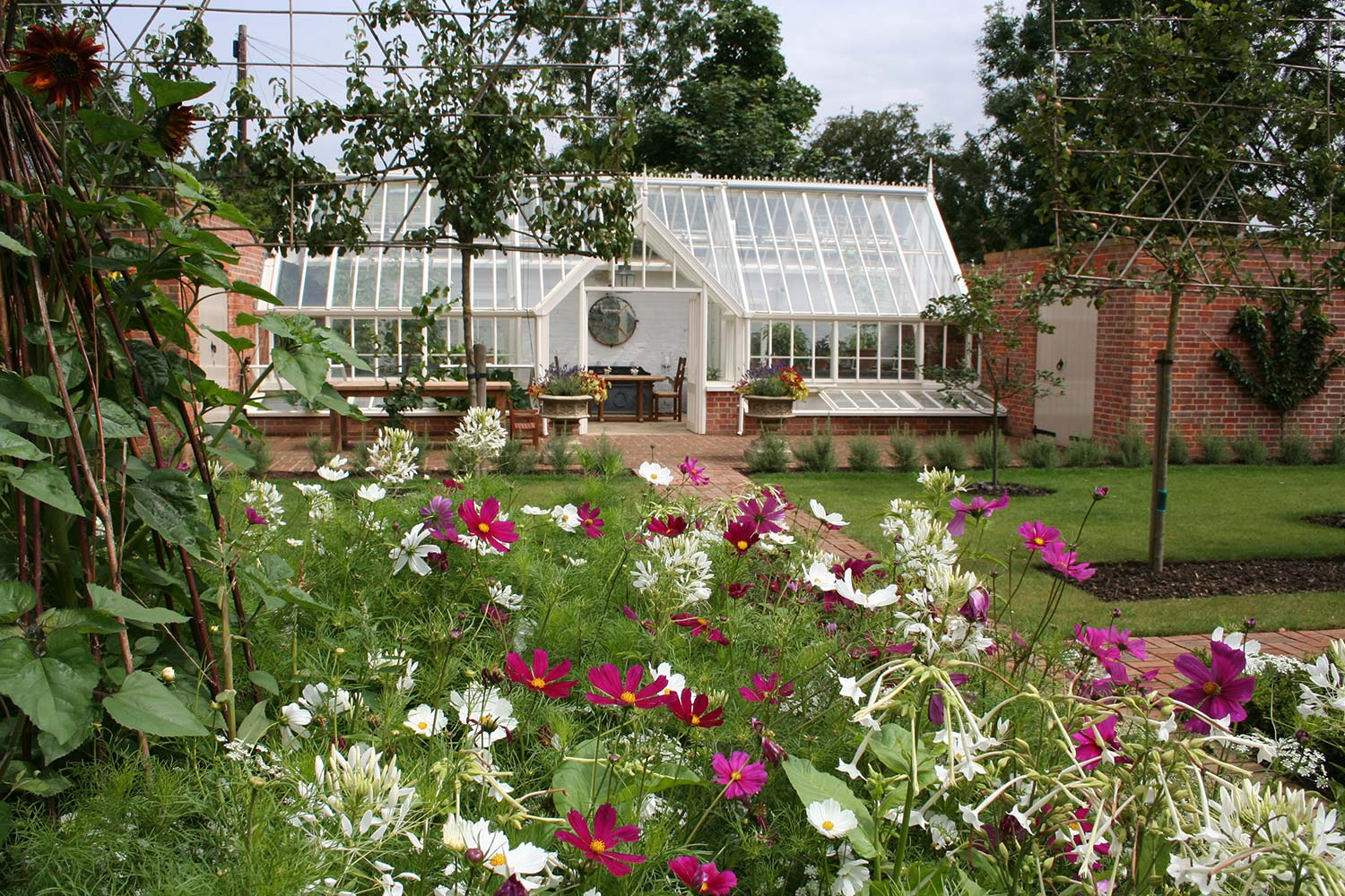 A half-span lean-to glasshouse attached to walls at both gable ends with a double lobby and cold frames (Alitex)
