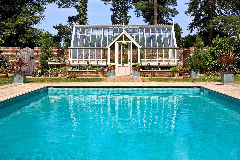 Et three-quater span, lean-to, pool side drivhus i farven Woodsage med finialer, mistbænke og mistbænke.
