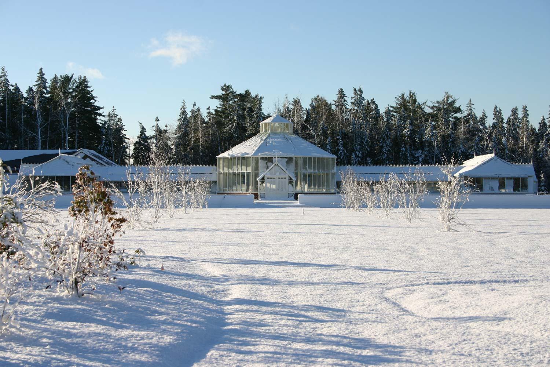 Et stor-skala fritstående oktagonalt drivhus med store sidevinger og to dobbelte lobbies I farven off-white.