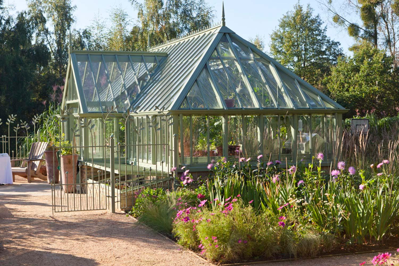 Et attraktivt fritstående drivhus med afvalmet tag i farven Sussex Emerald.