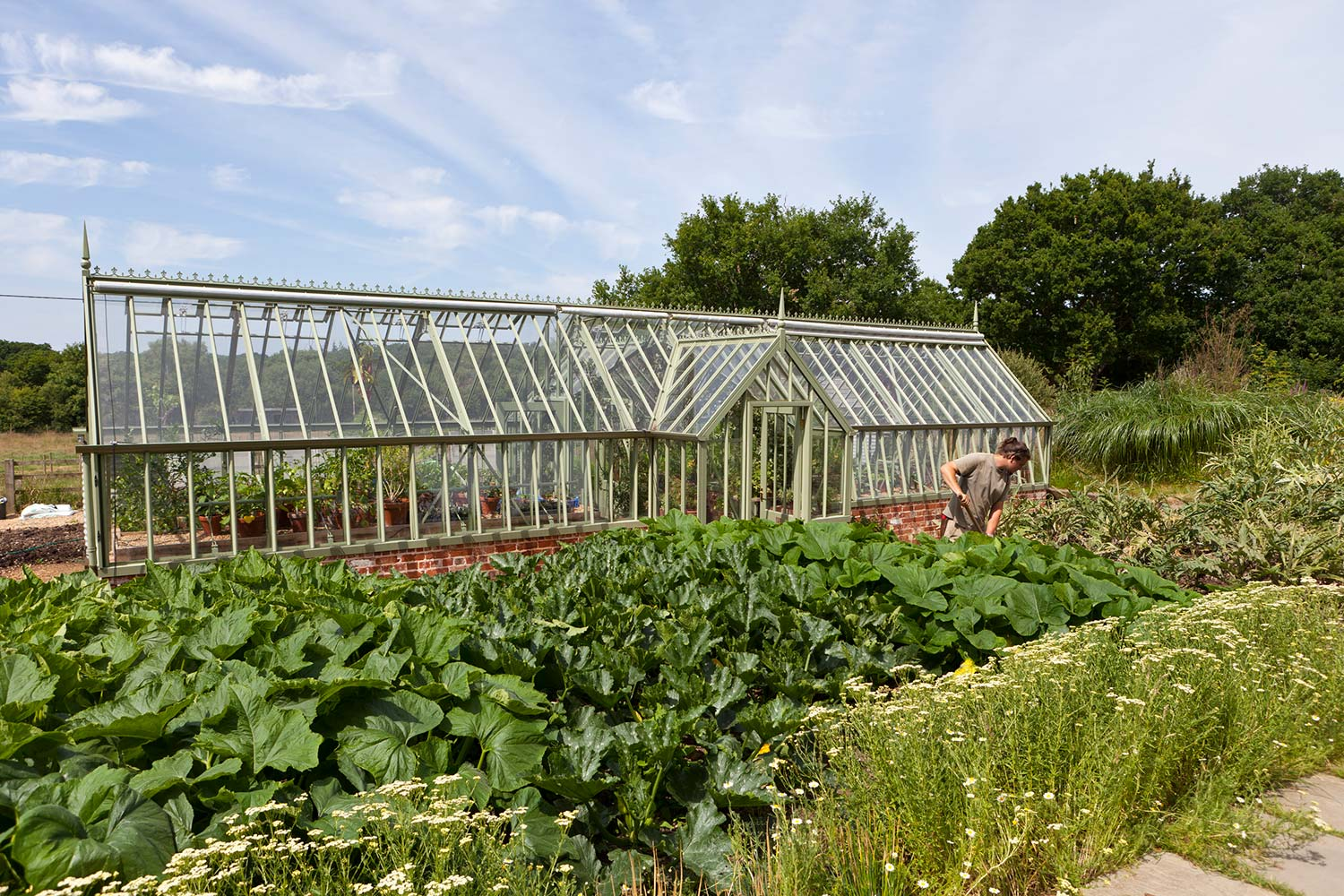 A freestanding greenhouse in Sussex Emerald with single lobbies at both front and back (Alitex)
