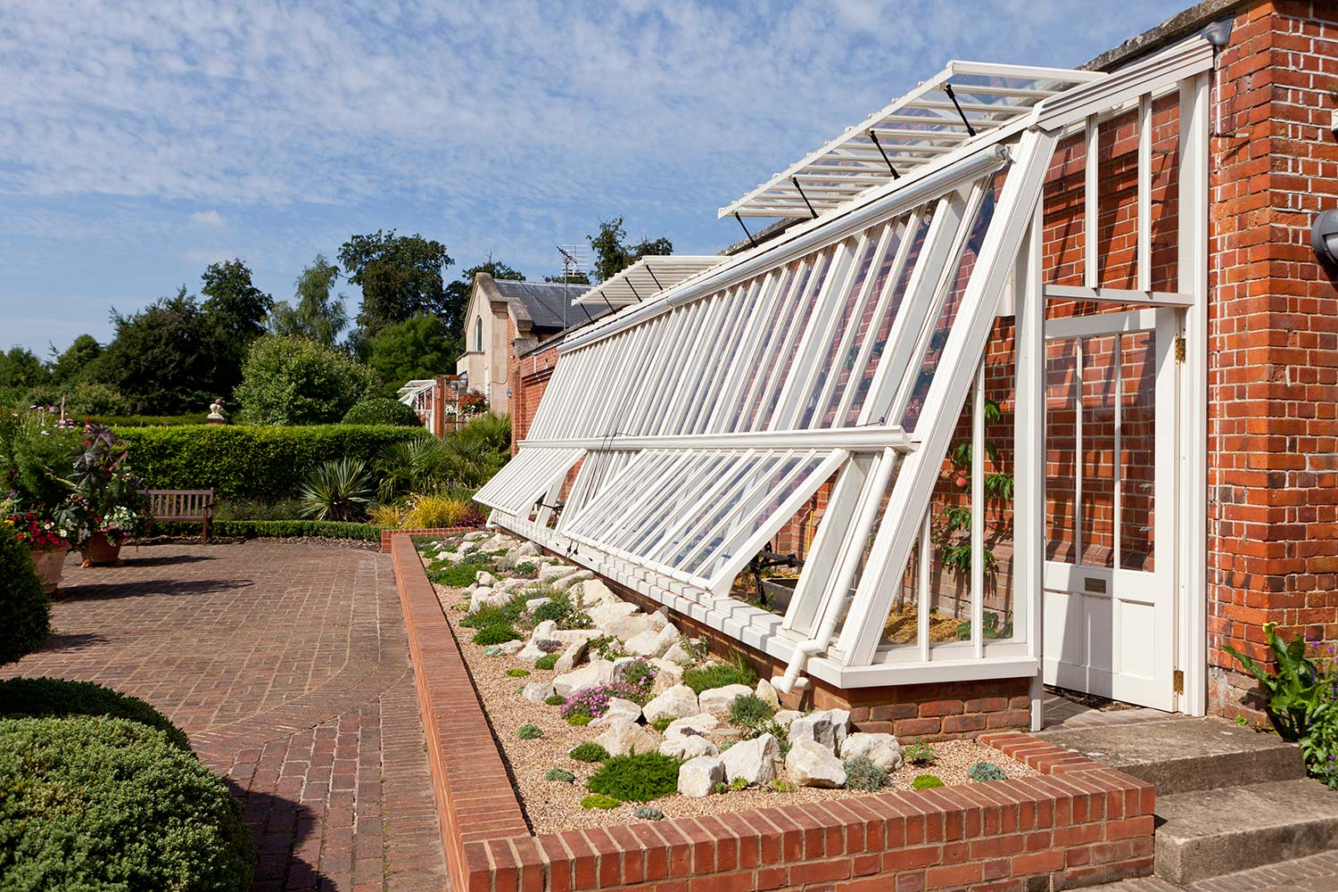 A monopitch lean-to greenhouse designed as a peach house with a sloping side in Off-white (Alitex)