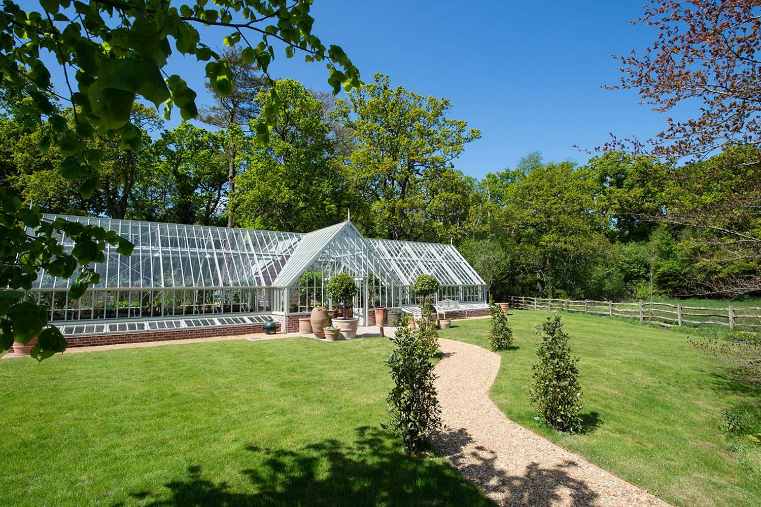 A freestanding greenhouse in Wood-Sage, in a cruciform shape with ample growing space in either wing (Alitex)