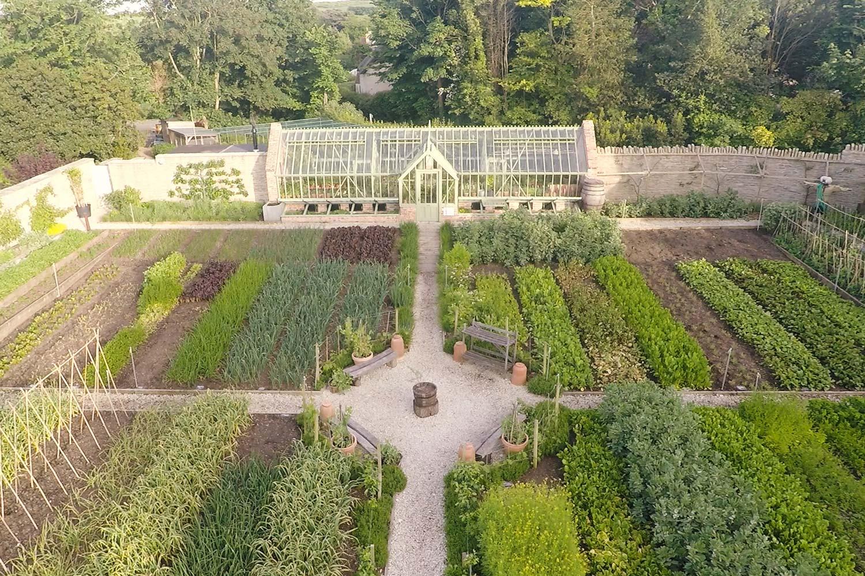 Et fritstående drivhus med begge gavle til muret væg, en enkeltdørs-lobby på begge sider og en imponerende have til en tilhørende Restaurant.